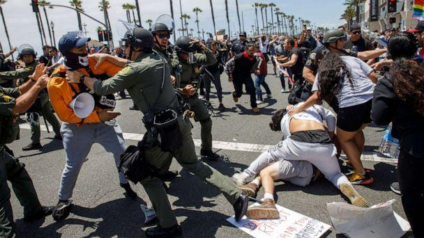 PHOTO: Black Lives Matter protesters fight with supporters of US President Donald Trump as police try to break up the clashes during a demonstration due to the police killing of George Floyd in Huntington Beach, California, June 6, 2020. (EUGENE GARCIA/EPA via Shutterstock)
