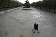 People walk in the empty Tuileries gardens Wednesday, Oct.14, 2020 in Paris. French President Emmanuel Macron is giving a nationally televised interview Wednesday night to speak about the virus, his first in months. French media reports say Macron will also step up efforts on social media to press the need for virus protections among young people. (AP Photo/Lewis Joly)