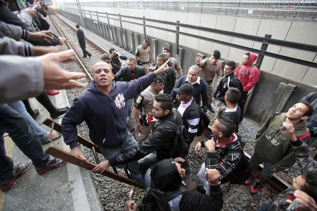 Police officers evacuate commuters from the railroads tracks at Itaquera subway station in Sao Paulo June 5, 2014. Union workers of Sao Paulo's Metro subway system are on strike since midnight, with just a week to go before the 2014 World Cup opens in Brazil, local media reported. The commuters broke the gate, which was closed due to the strike, to get access to the train to go to work. REUTERS/Chico Ferreira (BRAZIL - Tags: SPORT SOCCER WORLD CUP CIVIL UNREST POLITICS TRANSPORT)