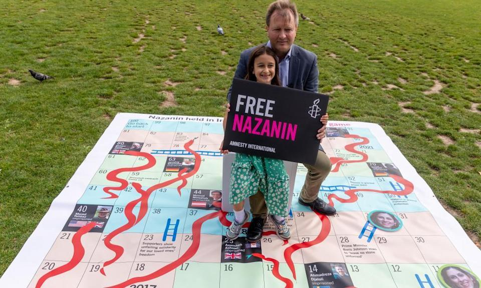 Richard and Gabriella Ratcliffe pose on a giant snakes-and-ladders board with a banner for Nazanin Zaghari-Ratcliffe who is detained in Iran.