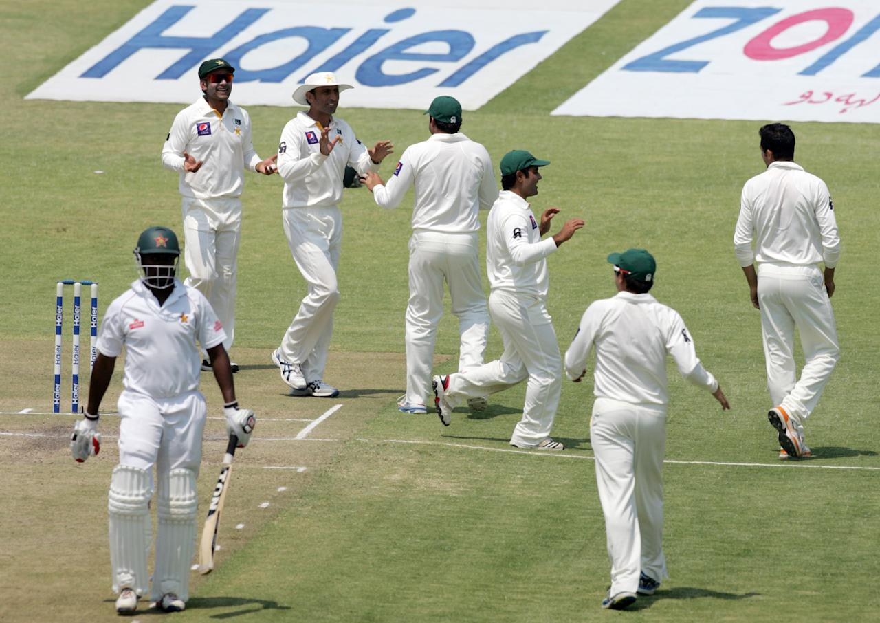 Pakistan players celebrates a wicket Elton Chigumbura during the fourth day of the second test match between Pakistan and hosts Zimbabwe at the Harare Sports Club on September 13, 2013. AFP PHOTO / JEKESAI NJIKIZANA        (Photo credit should read JEKESAI NJIKIZANA/AFP/Getty Images)