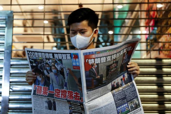 A supporter of Apple Daily newspaper, reads a copy of Apple Daily newspaper to support media mogul Jimmy Lai Chee-ying, founder of Apple Daily after he was arrested by the national security unit, in Hong Kong
