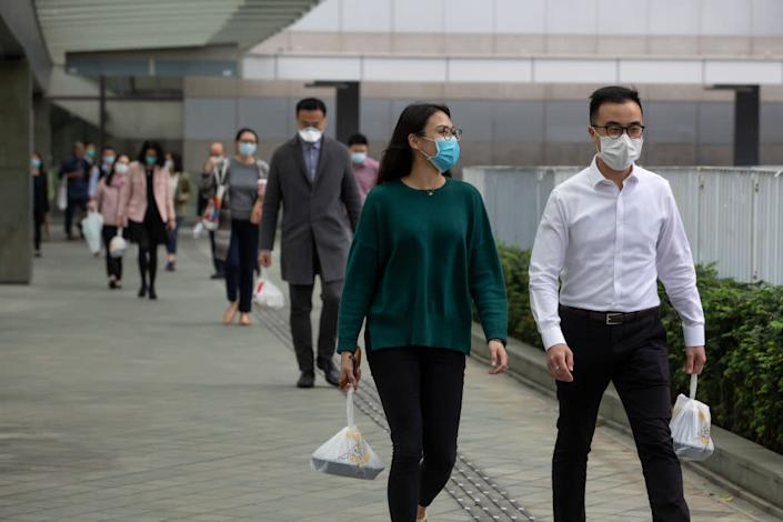 Office workers wearing masks carry take-out lunch orders while walking towards in Admiralty, Hong Kong, on Mar. 2, 2020. | Paul Yeung—Bloomberg/Getty Images