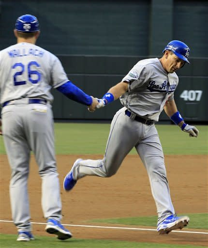 Los Angeles Dodgers' Matt Treanor, right, rounds the bases after hitting a two-run home run against the Arizona Diamondbacks and gets a handshake from third base coach Tim Wallach (26) during the second inning of a baseball game, Monday, May 21, 2012, in Phoenix. (AP Photo/Ross D. Franklin)
