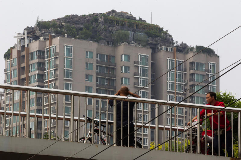 A man looks at a roof top villa with binoculars from an overhead bridge in Beijing, China, Tuesday, Aug. 13, 2013. Beijing authorities are planning to demolish the bizarre rooftop villa embedded in rocks, trees and bushes that allegedly was built illegally atop a 26-story apartment block in the capital. (AP Photo/Ng Han Guan)