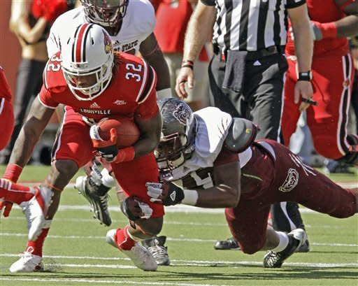 Louisville running back Senorise Perry (32) tries to get away from Missouri State's Rodney Kelly (47) during the first half of an NCAA college football game in Louisville, Ky., Saturday, Sept. 8, 2012. (AP Photo/Garry Jones)