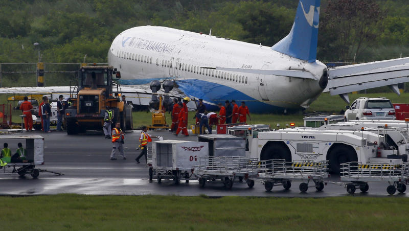 Xiamen Air a Boeing passenger plane from China sits on the grassy portion of the runway of the Ninoy Aquino International Airport after it skidded off the runway while landing Friday Aug. 17 2018 in suburban Pasay city southeast of Manila Philippines