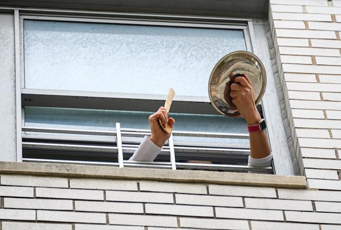 A person applauds from their window to show their gratitude to medical staff and essential workers working on the front lines of the coronavirus pandemic in New York City, May 18, 2020. (Photo by Noam Galai/Getty Images)