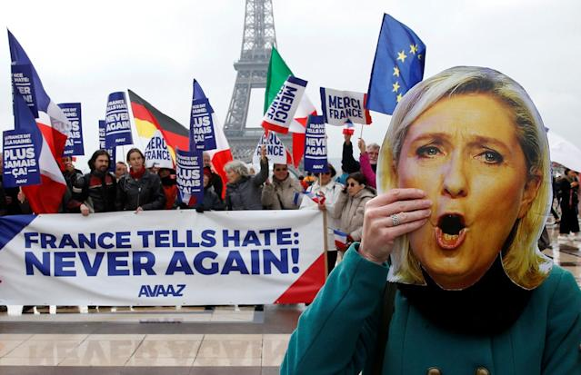 <p>A person holds a mask of France's National Front (FN) presidential candidate Marine Le Pen, as people gather with French and European Union flags near the Eiffel Tower the day after France's presidential elections, in Paris, May 8, 2017. (Pascal Rossignol/Reuters) </p>