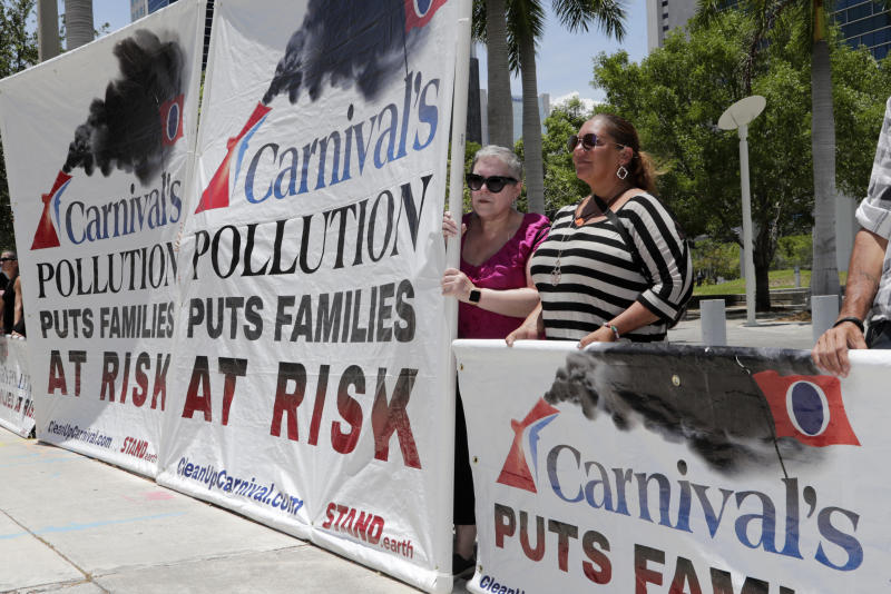 FILE - In this June 3, 2019 file photo, protesters with Stand.earth hold a banner in opposition to Carnival Corp. outside of federal court, in Miami. Top Carnival Corp. executives are due back in court to explain what the world's largest cruise line is doing to reduce ocean pollution. A hearing is set Wednesday, Oct. 2, 2019, in Miami federal court for an update on what steps Carnival is taking. (AP Photo/Lynne Sladky, File)