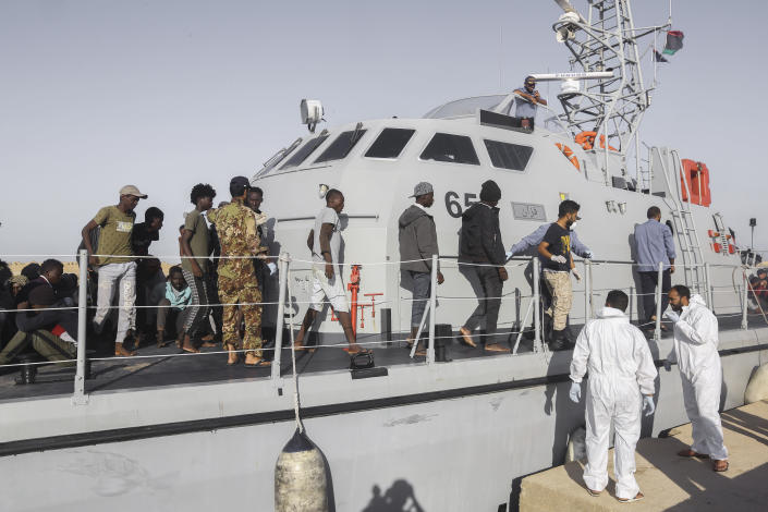 Rescued migrants walk off a coast guard boat in the city of Khoms, around 120 kilometers (75 miles) east of Tripoli, Libya, Tuesday, Oct. 1, 2019. (AP Photo/Hazem Ahmed)
