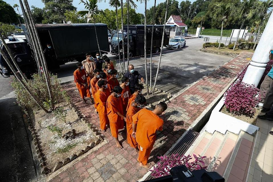 A group of men are led to the Bukit Mertajam Court to be remanded after a video clip of them performing Aidiladha prayers outside the Taman Pelangi Surau in Juru went viral on social media July 21, 2021. — Picture by Sayuti Zainudin