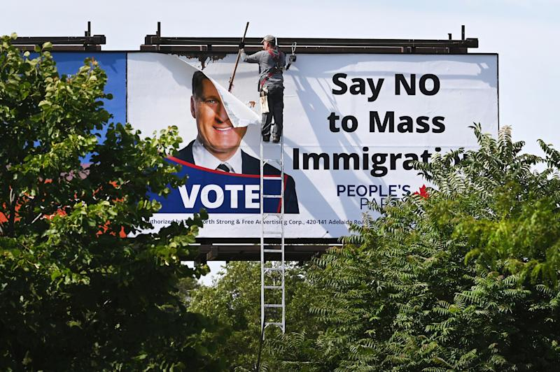 """A worker removes a billboard featuring the portrait of People's Party of Canada (PPC) leader Maxime Bernier and its message """"Say NO to Mass Immigration"""" in Toronto, Ontario, Canada August 26, 2019. REUTERS/Moe Doiron"""