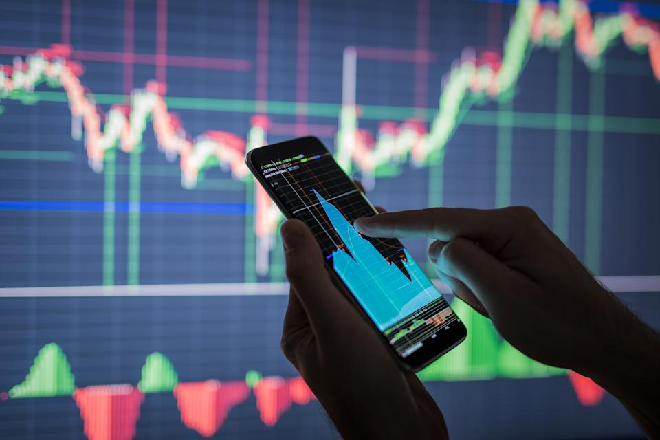 Businessman checking stock market data. He using a mobile phone. Analysis economy data on forex earn graph.