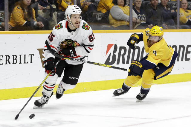 Nashville Predators defenseman Ryan Ellis (4) tries to slow down Chicago Blackhawks center Andrew Shaw (65) during the first period of an NHL hockey game Tuesday, Oct. 29, 2019, in Nashville, Tenn. (AP Photo/Mark Humphrey)
