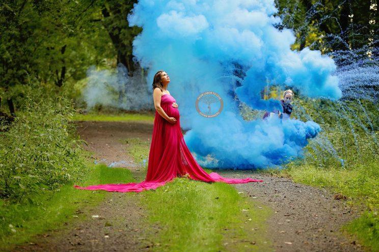 Pregnant woman stands in front of blue smoke