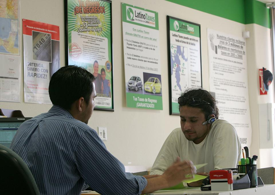 An accountant helps a customer with his taxes at Latino Taxes in Oakland, California. (Photo: Justin Sullivan/Getty Images)