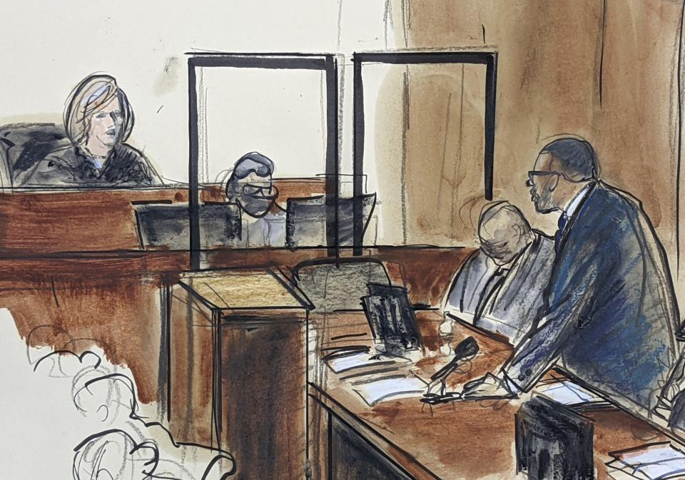 In this illustration drawn from a video feed, R. Kelly, right, stands and responds to Judge Ann Donnelly's question whether or not he has decided to take the stand in his own defense, Wednesday, Sept. 22, 2021, in New York. (AP Photo/Elizabeth Williams)