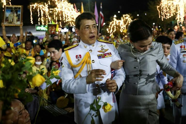 Thai King Maha Vajiralongkorn and Queen Suthida greet supporters as they leave the palace
