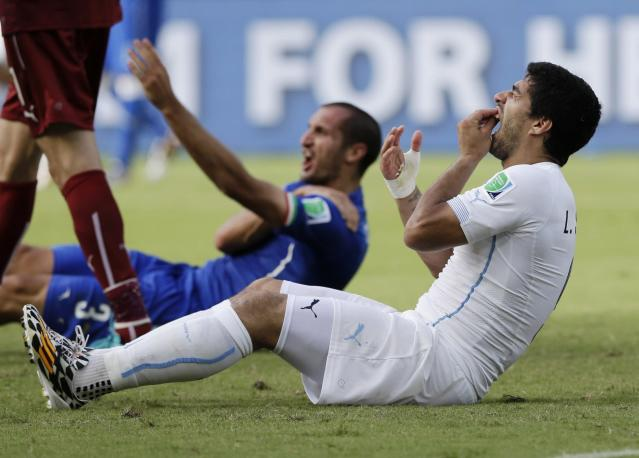 FILE - In this June 24, 2014 file photo, Uruguay's Luis Suarez holds his teeth after biting Italy's Giorgio Chiellini's shoulder during the group D World Cup soccer match between Italy and Uruguay at the Arena das Dunas in Natal, Brazil. The 21st World Cup gets underway on Thursday, June 14, 2018 in Moscow when host Russia takes on Saudi Arabia. (AP Photo/Ricardo Mazalan, File)