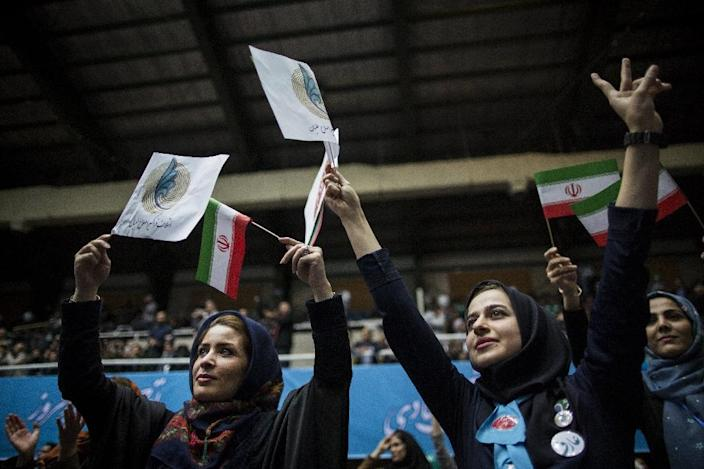 Iranian women hold reformists and national flags during a reformists campaign meeting for the parliamentary elections in downtown Tehran on February 20, 2016 (AFP Photo/Behrouz Mehri)