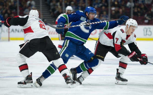Vancouver Canucks center Zack MacEwen (71) fights for control of the puck with Ottawa Senators defenseman Dylan DeMelo (2) and left wing Brady Tkachuk (7) during the second period of an NHL hockey game Tuesday, Dec. 3, 2019, in Vancouver, British Columbia. (Jonathan Hayward/The Canadian Press via AP)