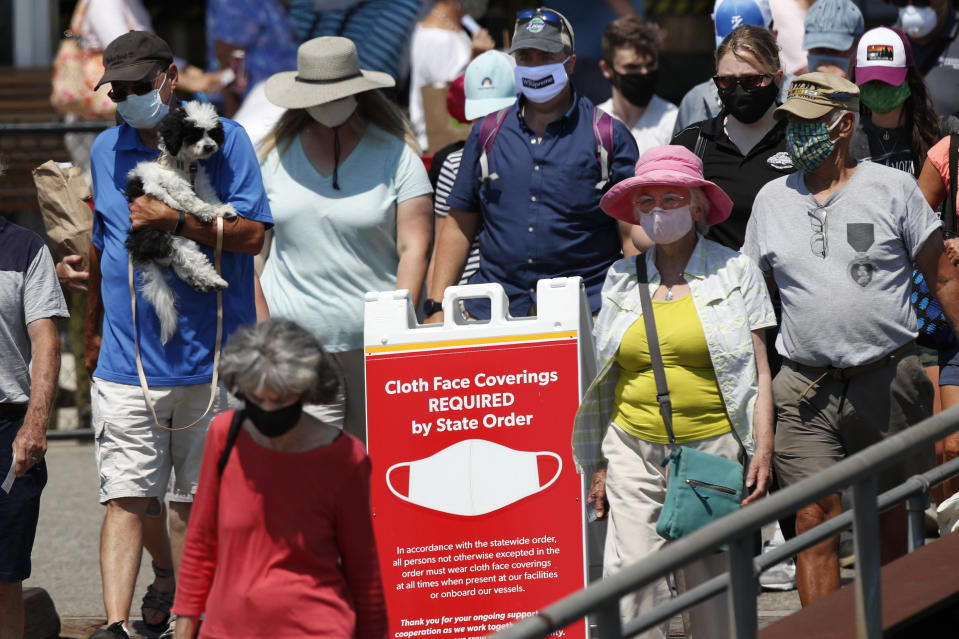 Passengers boards a Casco Bay Lines ferry bound for Peaks Island, Thursday, July 30, 2020, in Portland, Maine. State officials reported more cases of COVID-19. (AP Photo/Robert F. Bukaty)
