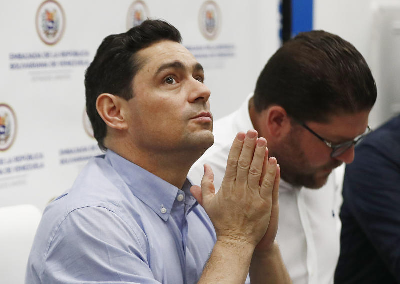 Carlos Vecchio, center, a government opponent who the U.S. recognizes as Venezuela's ambassador, gestures as he speaks during a news conference on Tuesday, June 11, 2019, in Miami. President Donald Trump says his administration is considering granting Temporary Protected Status to thousands of Venezuelans including Vecchio who have fled to the United States amid ongoing unrest. (AP Photo/Brynn Anderson)