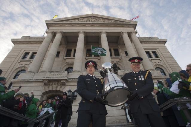 Regina City Police bring the Grey Cup out of the Saskatchewan Legislative building after the Grey Cup parade on Tuesday, Nov. 26, 2013 in Regina, Saskatchewan. The Saskatchewan Roughriders defeated the Hamilton Tiger-Cats 45-23 in the 101st CFL Grey Cup on Sunday. (AP Photo/The Canadian Press, Liam)