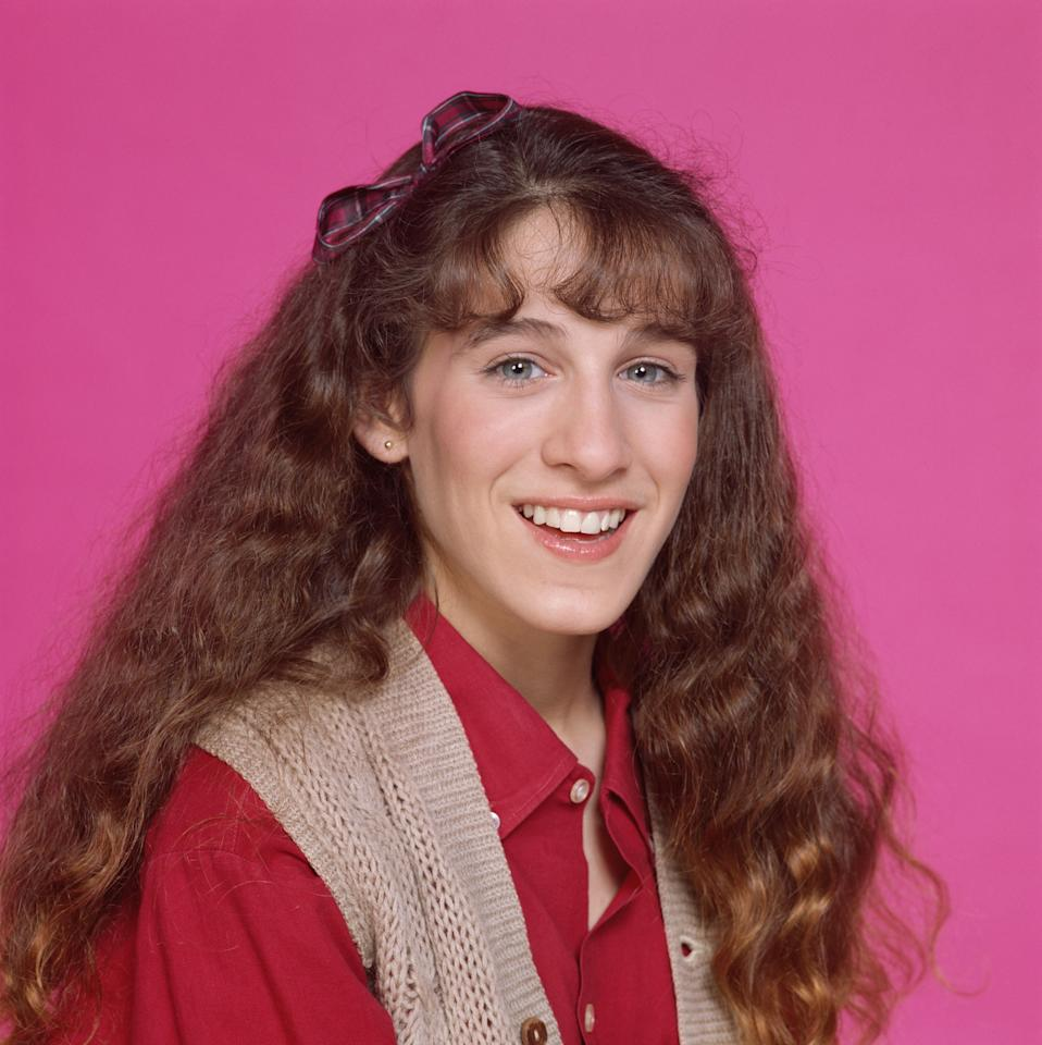 """<p>Sarah Jessica Parker with long hair and bangs on the set of """"Square Pegs,"""" a CBS situation comedy. She tops the look off with a bow clip.</p>"""