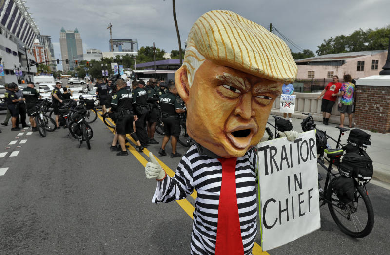 A protestor wearing a large President Donald Trump head walks near law enforcement officers during a rally Tuesday, June 18, 2019, in Orlando, Fla. A large of protestors were holding a rally near where Trump was announcing his re-election campaign. (AP Photo/Chris O'Meara)