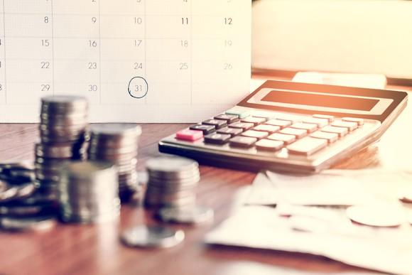Calculator and coins on desk with calendar.