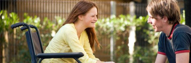 Young woman in wheelchair with male friend.