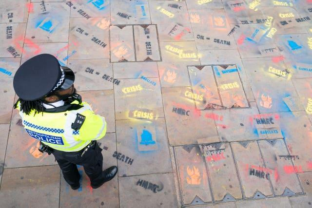 A police officer stands among slogans sprayed onto the pavement outside the offices of HM Revenue and Customs