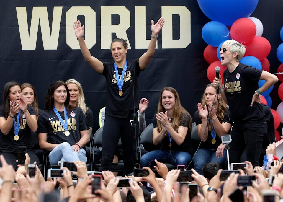 U.S. women's soccer team midfielder Megan Rapinoe, right, introduces teammate Carli Lloyd during a public rally held to celebrate the team's World Cup championship, Tuesday, July 7, 2015, in Los Angeles. This was the first U.S. stop for the team since beating Japan in the Women's World Cup final Sunday in Canada. (AP Photo/Jae C. Hong)