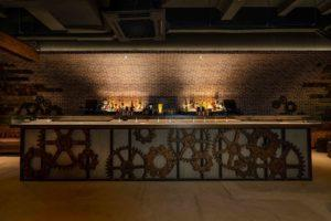 Visualization of the glass-paneled bar with exposed brass pipes. Image: Rails