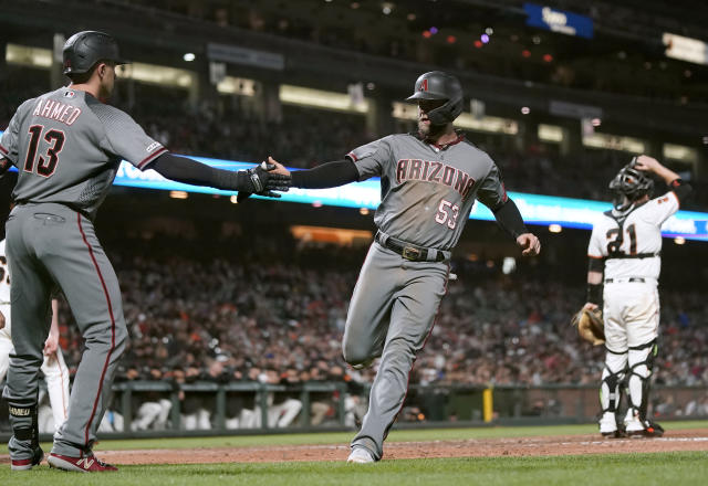 Arizona Diamondbacks' Christian Walker (53) is congratulated by teammate Nick Ahmed (13) after he scored on a single by Adam Jones against the San Francisco Giants during the sixth inning of a baseball game in San Francisco, Tuesday, Aug. 27, 2019. (AP Photo/Tony Avelar)