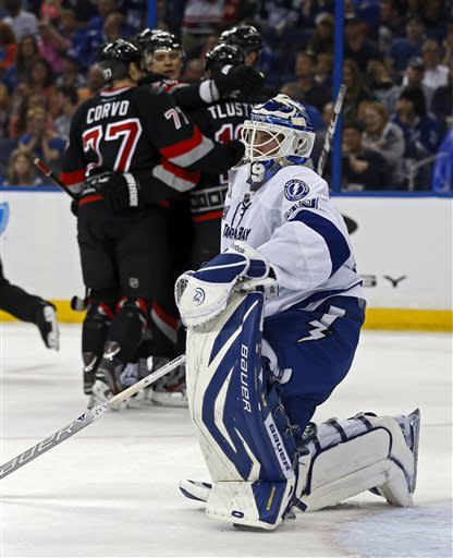 Tampa Bay Lightning goalie Anders Lindback, of Sweden, reacts to allowing the third goal of the first period as members of the Carolina Hurricanes celebrate in the background during an NHL hockey game, Sunday, April 21, 2013, in Tampa, Fla. (AP Photo/Mike Carlson)