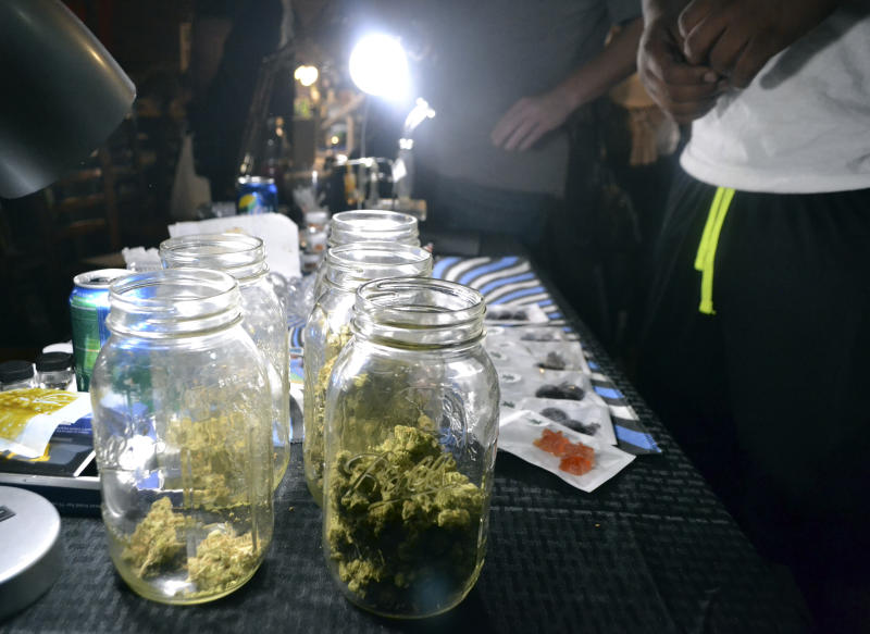 "In this Sept. 11, 2017, photo, jars of marijuana buds are displayed in Washington at a closed Ethiopian restaurant at a ""gifted"" marijuana event. In the so-called ""District of Cannabis"" it's legal to grow and consume marijuana, but illegal to buy or sell it. The result of this unique legal grey area has spawned a thriving cottage industry of businesses using the ""gifting"" loophole. So far the city government and police are letting it happen. (AP Photo/P. Solomon Banda)"