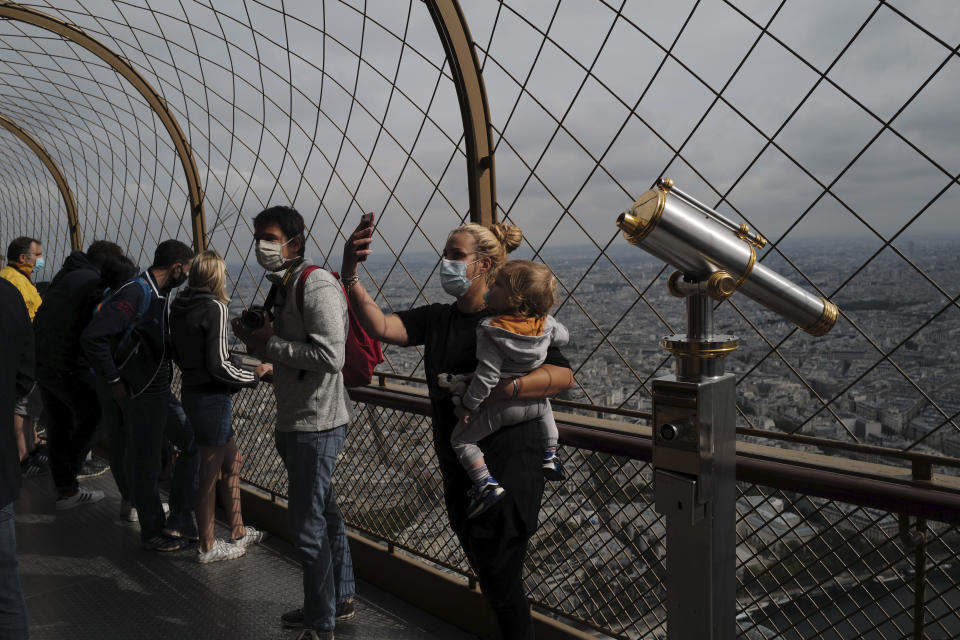 French visitors take a selfie from the third level during the opening up of the top floor of the Eiffel Tower, Wednesday, July 15, 2020 in Paris. The top floor of Paris' Eiffel Tower reopened today as the 19th century iron monument re-opened its first two floors on June 26 following its longest closure since World War II. (AP Photo/Francois Mori)