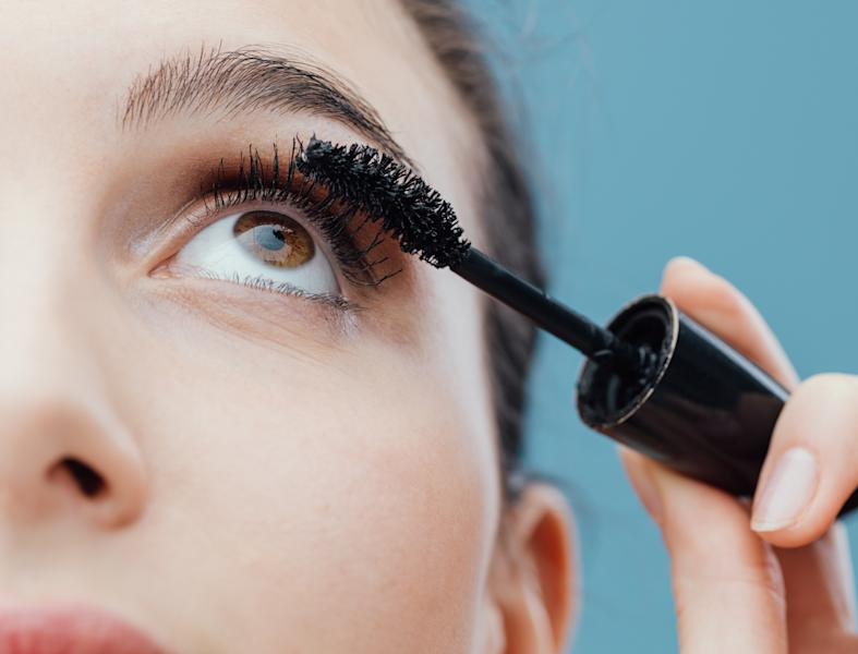 Woman applying mascara on her lashes, make up and cosmetics concept