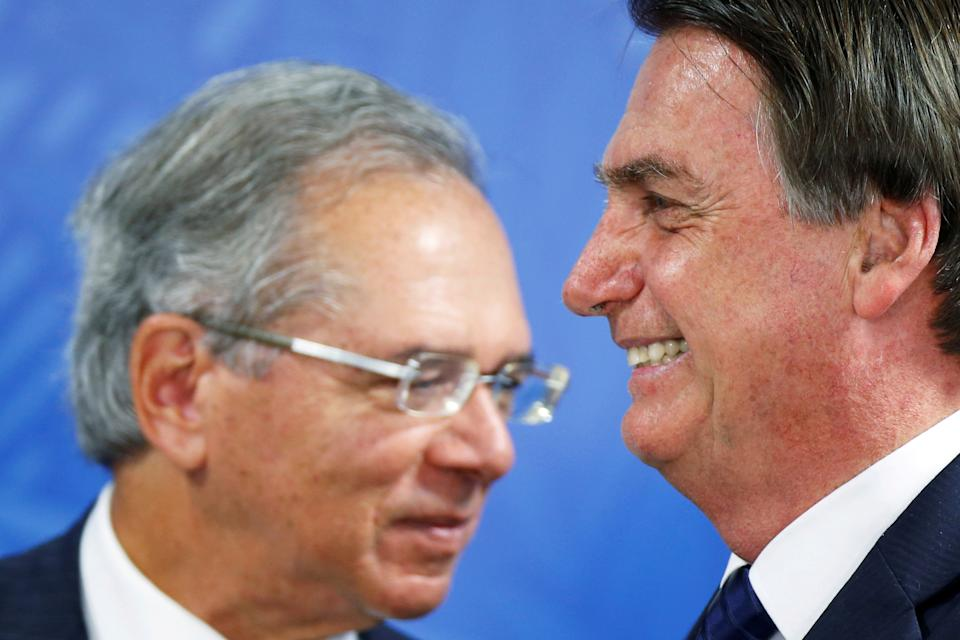 Brazil's President Jair Bolsonaro looks on near Brazil's Economy Minister Paulo Guedes during an inauguration ceremony of the new Brazilian National Development Bank (BNDES) President at the Planalto Palace in Brasilia, Brazil July 16, 2019. REUTERS/Adriano Machado     TPX IMAGES OF THE DAY