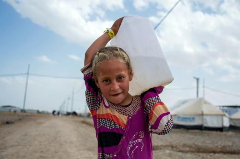 An Iraqi girl walks carrying water at a camp for internally displaced people in Hammam al-Alil after fleeing West Mosul due to the ongoing battles between government forces and Islamic State group jihadists