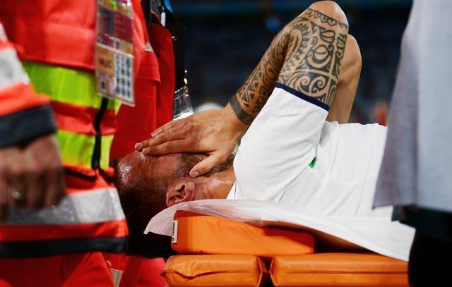 Italy's Leonardo Spinazzola covers his face as he is carried off on a stretcher
