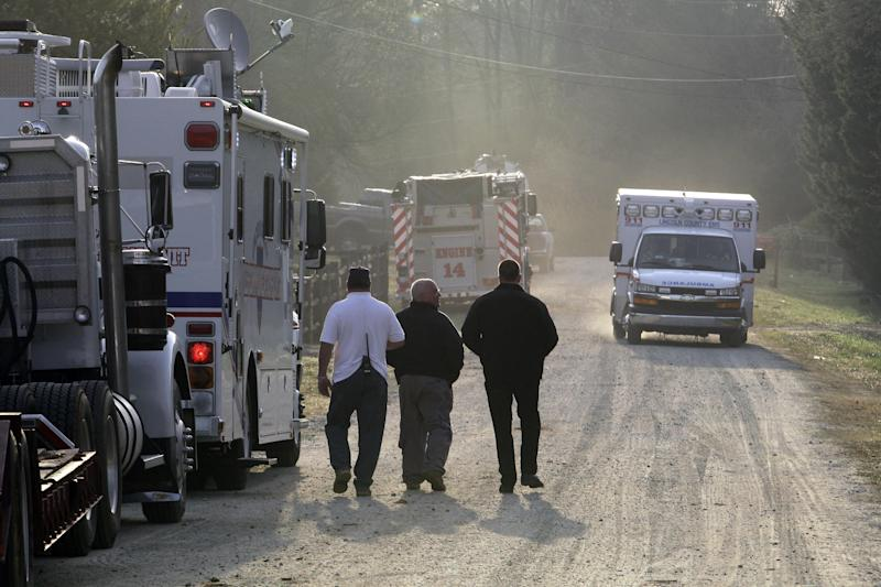 Fire and rescue personnel make their way down Cedarbrook Court, Monday, April 8, 2013, to the end of the road where two children died when a wall of dirt fell on them while they were playing in a hole at a construction site behind their home, on Sunday, in Stanley, N.C. (AP Photo/Bob Leverone)