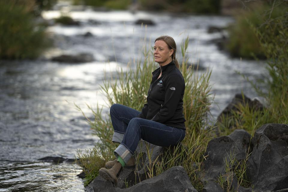 """Kate Fitzpatrick, the executive director of the Deschutes River Conservancy, poses for a press photo along the banks of the middle Deschutes River on Tuesday, Aug. 31, 2021, in Bend, Ore. """"We're trying to figure out ways for water to move around more flexibly,"""" she said. """"If we can find those win-win solutions, I believe that the Deschutes can be a model for the West as the West faces increasing drought and scarcity and population growth."""" (AP Photo/Nathan Howard)"""