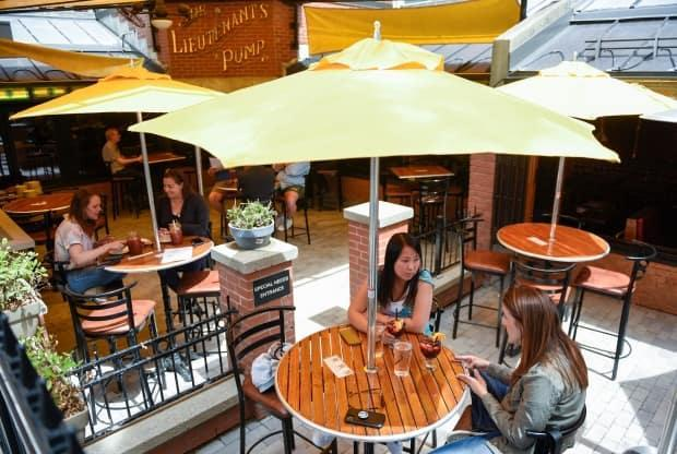 People in groups of two have drinks on an outdoor patio at The Lieutenant's Pump pub in Ottawa as patios opened in June. Indoor dining is set to open on Friday. (Justin Tang/The Canadian Press - image credit)