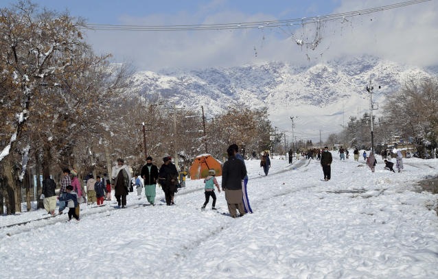People walk on a snow-covered road in Quetta, capital of Pakistan's southwestern Baluchistan province, Monday, Jan. 13, 2020. Severe winter weather has struck parts of Afghanistan and Pakistan with heavy snowfall, rains and flash floods that left more than 54 dead, officials said Monday as authorities struggled to clear and reopen highways and evacuate people to safer places. (AP Photo/Arshad Butt)