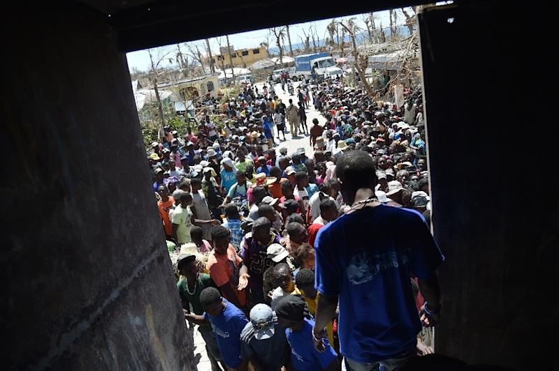 Hurricane Matthew victims wait to receive food from the UN's World Food Programme in Roche-a-Bateaux, in Les Cayes, in the south west of Haiti, on October 12, 2016