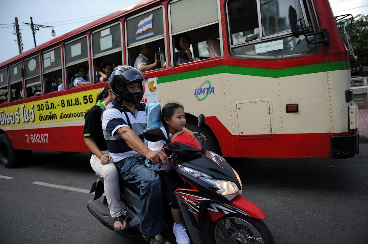 Seven-year-old Thai student Chamaya Pamutito rides a scooter as she travels back from school with her father and mother in Bangkok on June 6, 2013.